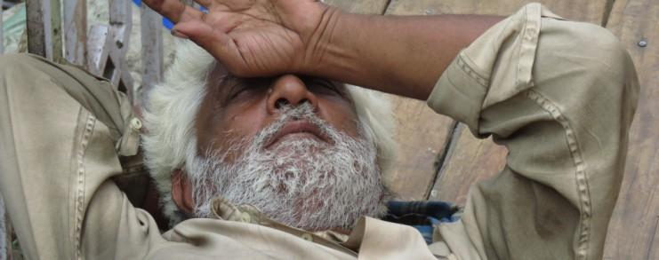Man shielding his face from the sun in Mumbai, India